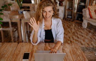 woman waving at a computer screen during a chat