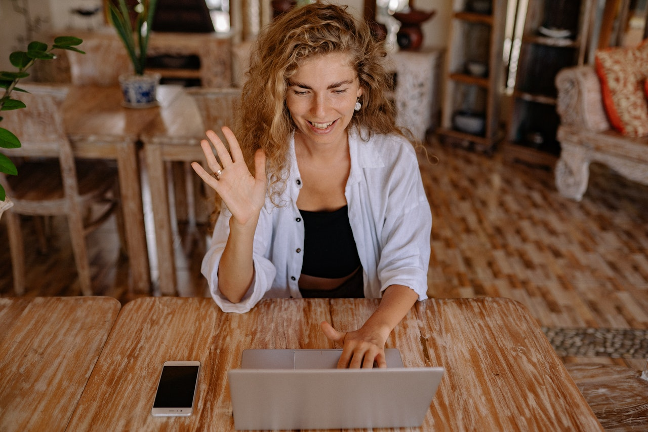 woman waving at a computer screen during a chat