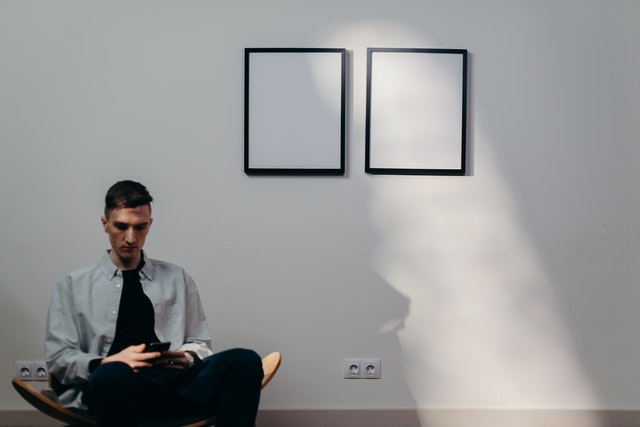 man sits in front of artwork looking at his phone