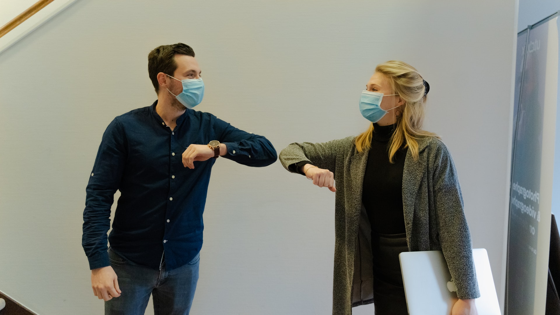 coworkers touch elbows in greeting