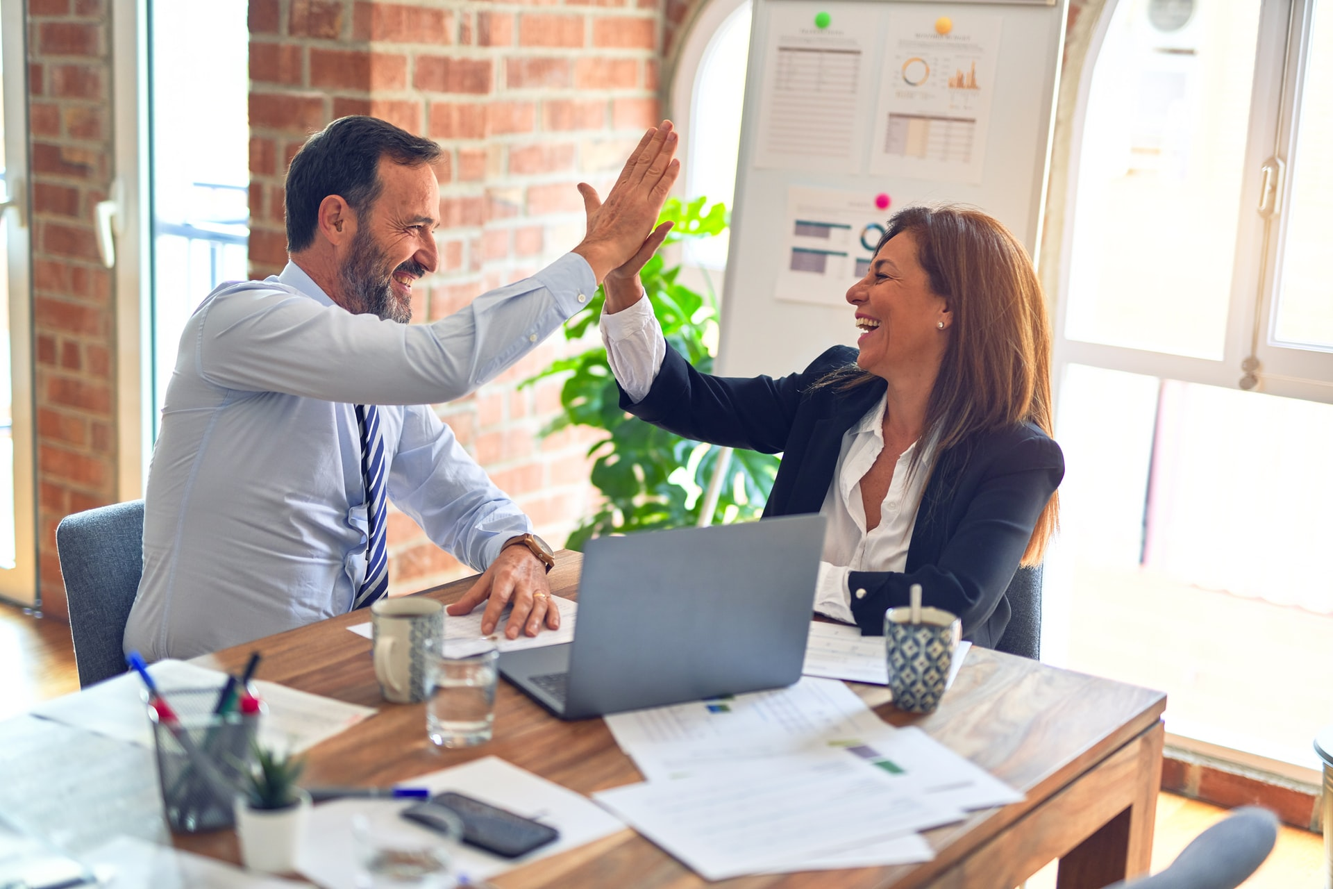 man and woman in business attire high five over a completed project